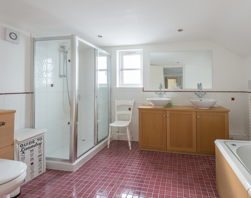 The master bedroom at Cliffside 1 has a spacious bathroom with a bath, shower and twin wash basins at this wonderful cliff top holiday house in Port Isaac.
