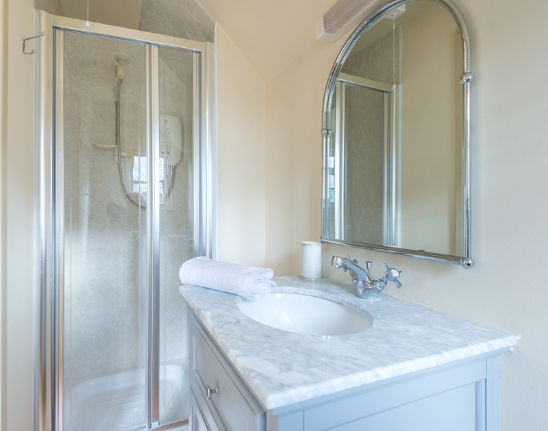 The light and bright shower room ensuite complete with a shower, WC and sink vanity unit.
