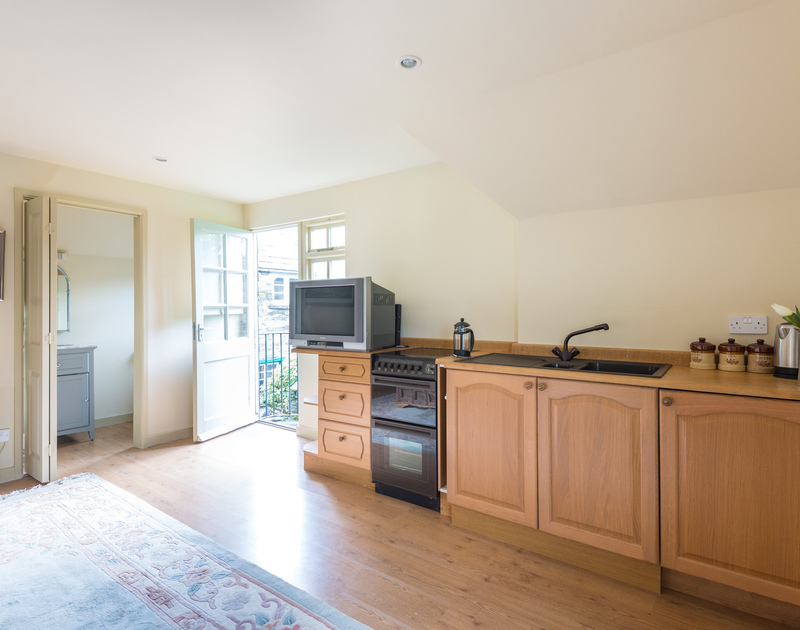 The traditional kitchen area in the annexe at Porthilly Greys complete with a cooker, fridge and sink to cook yourself a full english breakfast.
