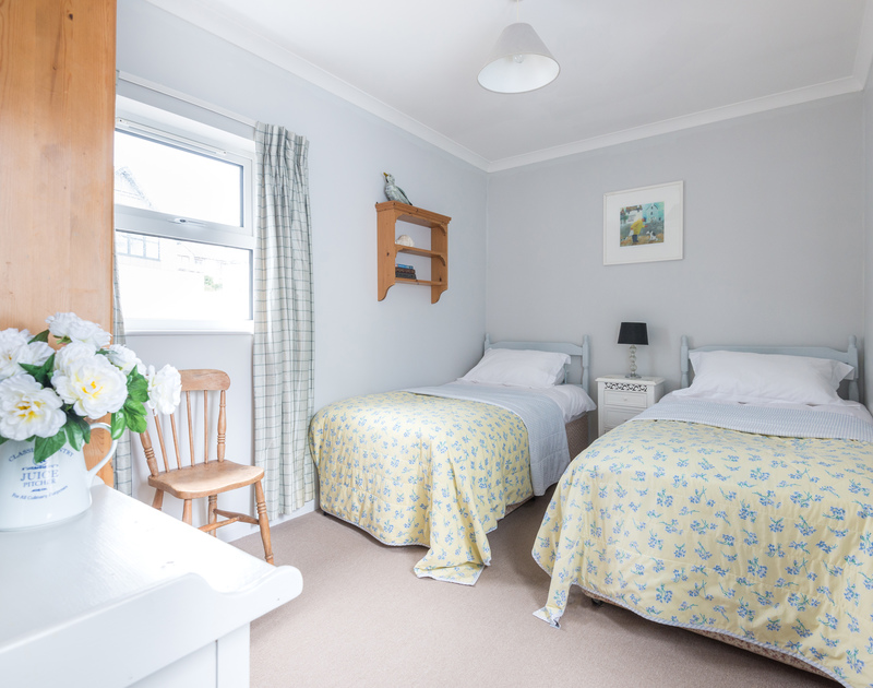 A cosy twin bedroom at Little Strand, a self-catering holiday rental in Rock, Cornwall