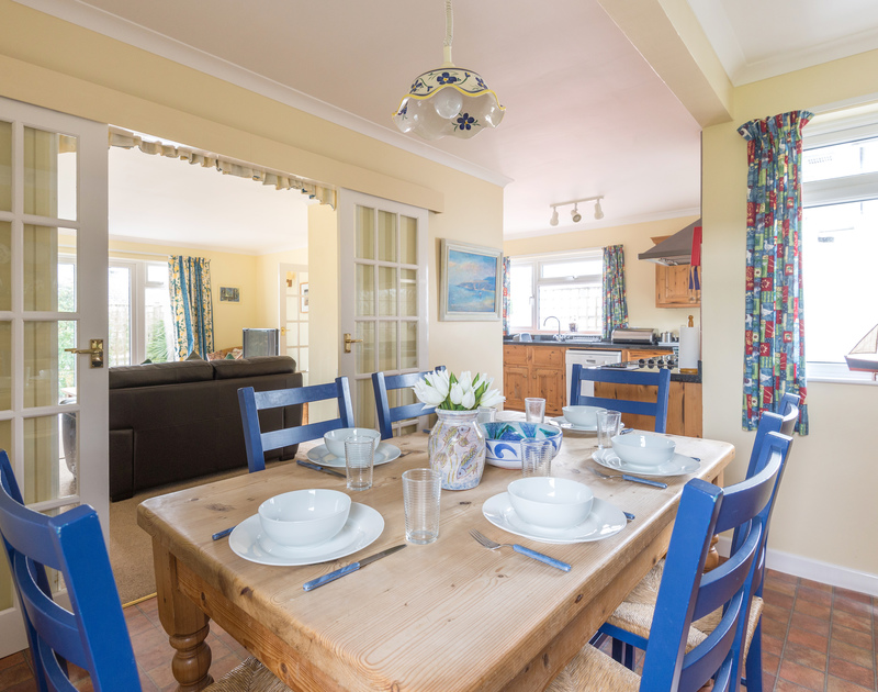 The bright dining table in the open plan kitchen/diner in Little Sailing, a self catering holiday rental in Rock on the north coast of Cornwall.