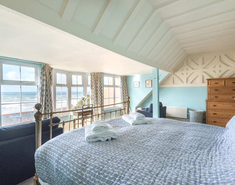 The comfortable master bedroom with stunning sea views at Pemberton, a self catering holiday house in peaceful New Polzeath, North Cornwall.