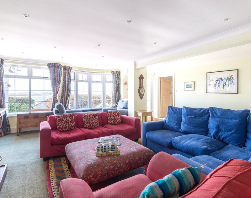 The large sitting room with stunning sea views from the pretty windows at Pemberton, a self catering holiday house to rent in New Polzeath, Cornwall.