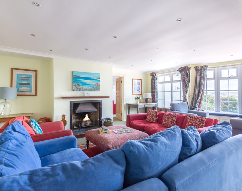 The sitting room at Pemberton showing the open fire and comfortable seating in this self catering, coastal holiday house in New Polzeath, Cornwall.