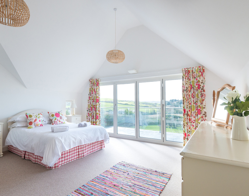 Another spacious ensuite bedroom with bifold doors out onto a private balcony with views over to Daymer Bay