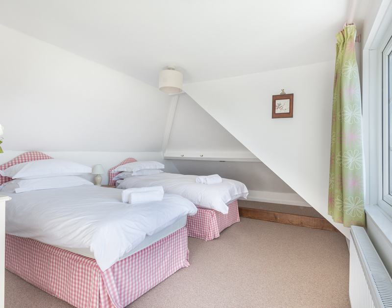 The light, twin bedroom on the left hand side with a bathroom ensuite at  Hob House, a luxurious self catering holiday property in Daymer Bay, Trebetherick, Cornwall.