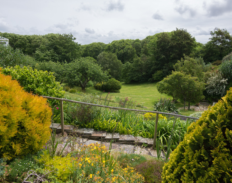 Rustic, wooden handrail and slated pathway with mature borders and the sweep of lawn beyond at Sliggon Field, a holiday haven for garden lovers, yet within easy reach of the coast.