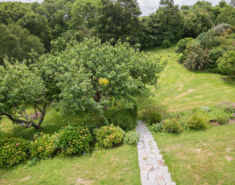 Follow the slate steps down into the enormous gardens at self catering, holiday house to rent Sliggon Field in Trebetherick in north Cornwall.