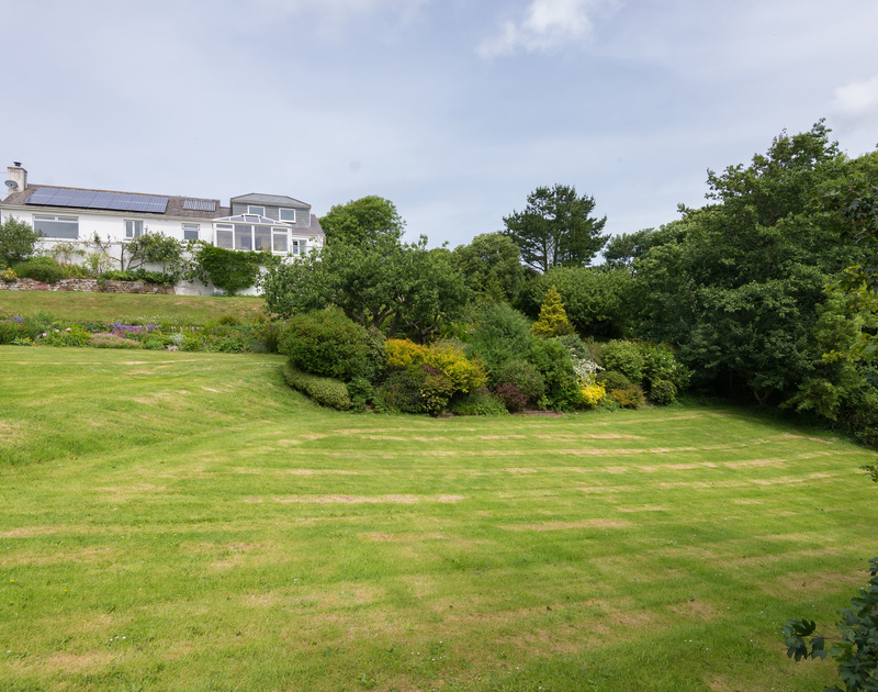 A huge expanse of  lawned garden wraps itself around the more wooded areas at self catering, Sliggon Field near Polzeath.