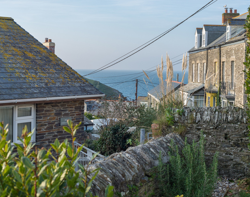 The view of the sea and horizon past Port Isaac's attractive stone houses from the corner of the garden at Morwenna, a self catering holiday house to rent in Port Issac.