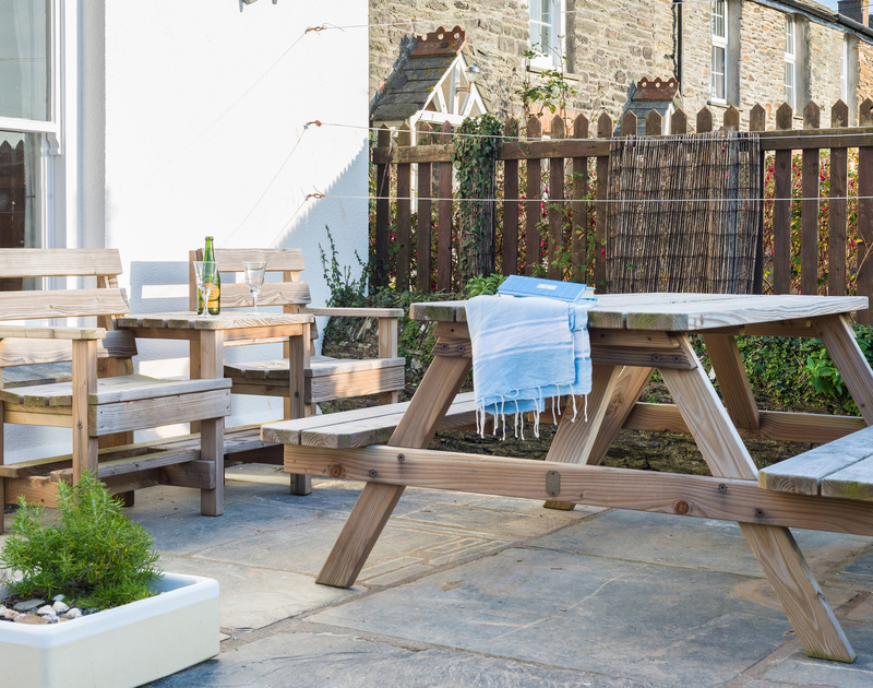 Large slate slabs soak up the sunshine on the sheltered terrace at Morwenna, a comfortable, family, self catering holiday house to rent in Port Isaac on the North Cornish Coast.