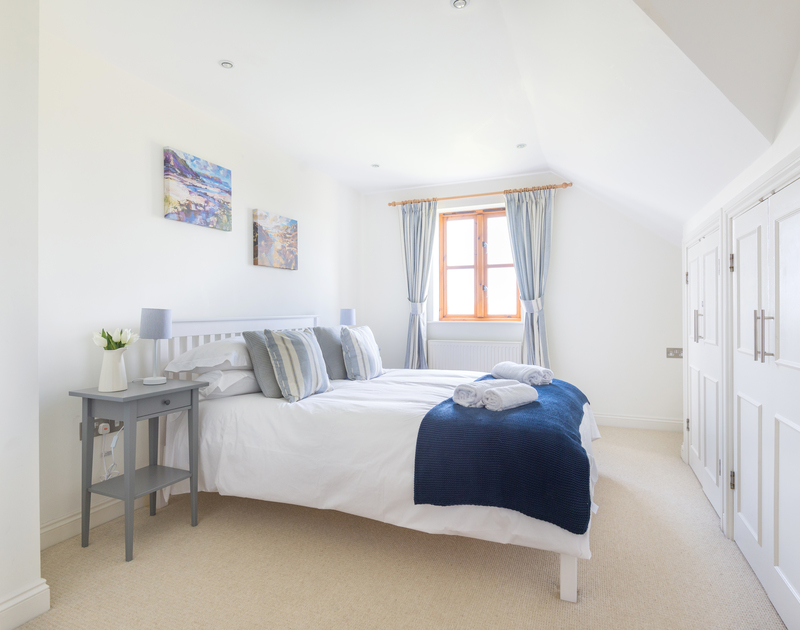 The master bedroom of Lundy Cottage, a self-catering holiday house in Rock, Cornwall, with ample storage space.