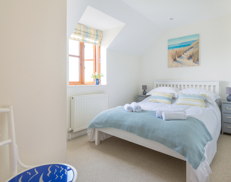 The modern double bedroom with plenty of storage and views over the garden at Lundy Cottage in Rock.