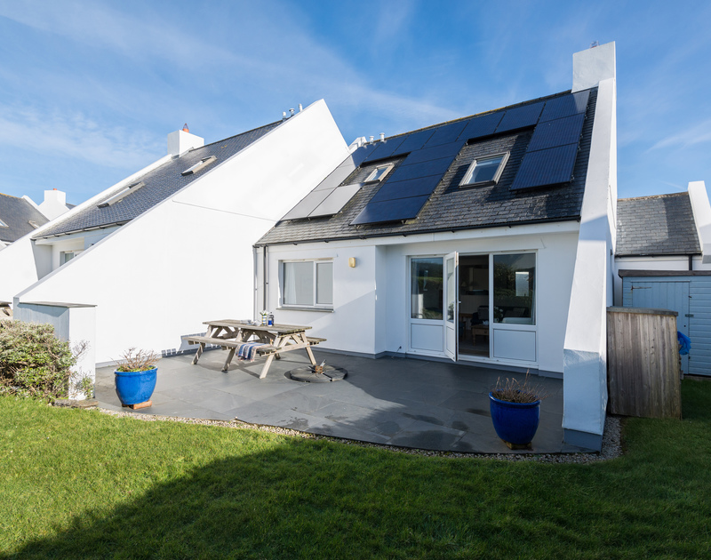 The exterior of Pengelly, a villa-style semi-detached holiday rental in Polzeath, Cornwall, with sunny paved patio and lawn.