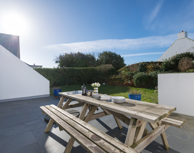 The back garden and patio with outdoor seating at Pengelly self catering holiday home in Polzeath, North Cornwall.