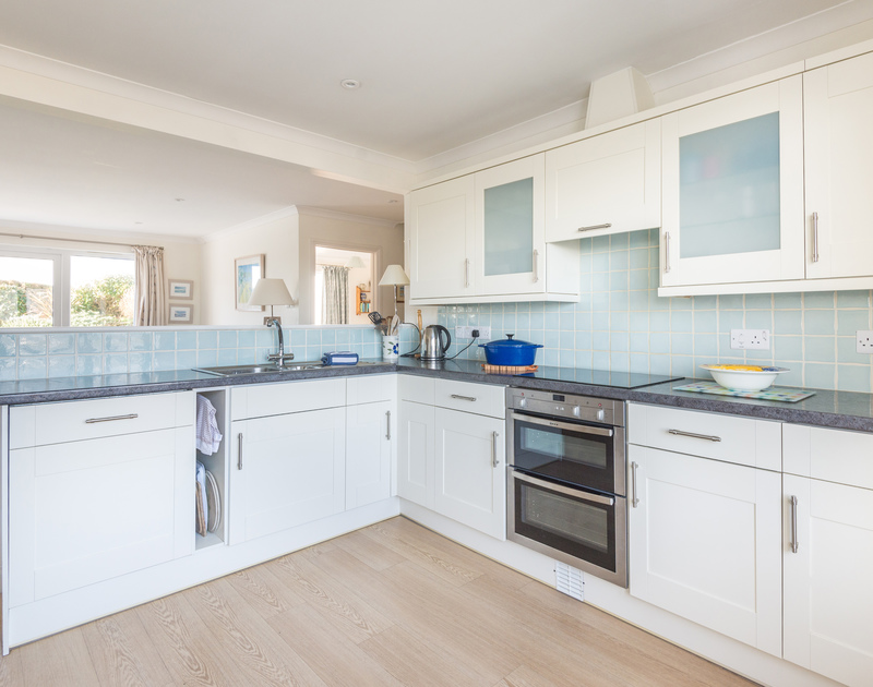 The stylish and modern kitchen of Pengelly, a holiday house to rent at Polzeath, Cornwall, with doors to the patio.