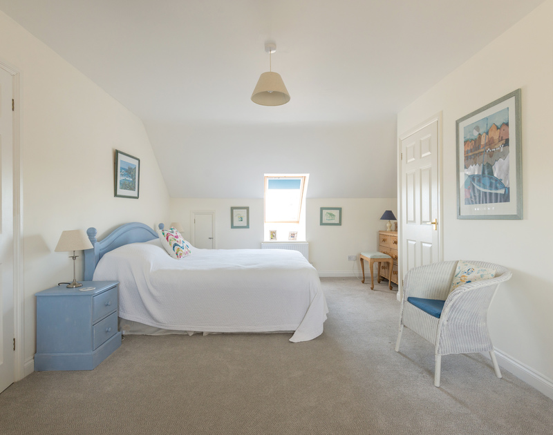 Coastal shades decorate the master bedroom at self catering holiday rental Pengelly in Polzeath.
