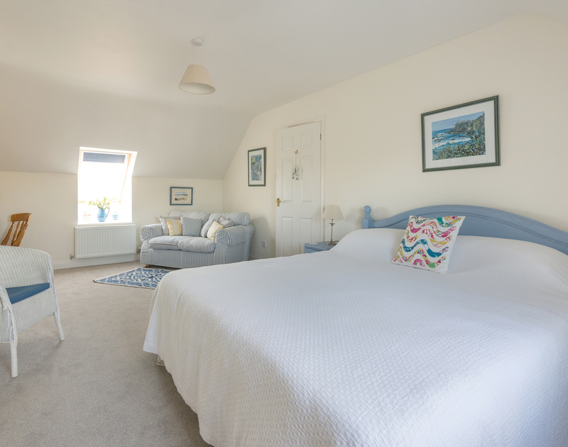 The spacious master double bedroom of Pengelly, a holiday house to rent in Polzeath, with its pretty bedspread and adjacent sofa.