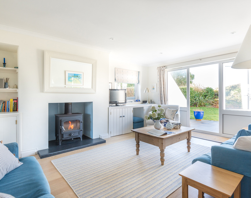 The comfy sitting room of Pengelly, a holiday rental in Polzeath, Cornwall, with warming wood burner.