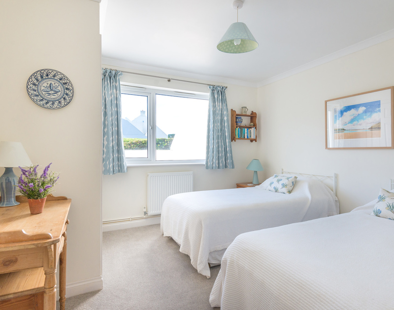 The well-furnished twin bedroom of Pengelly, a self-catering holiday rental in Polzeath, Cornwall