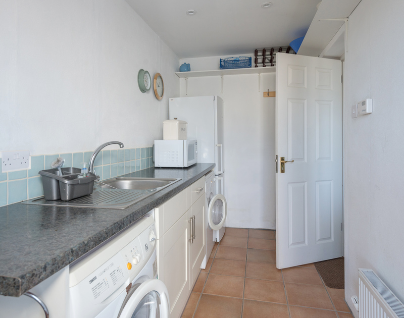 The utility room with a washing machine, tumble dryer, sink and fridge freezer at Pengelly.