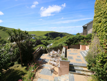 Coastal views from the terraced garden of Valencia House, a holiday house in Port Isaac, Cornwall, with patio furniture.