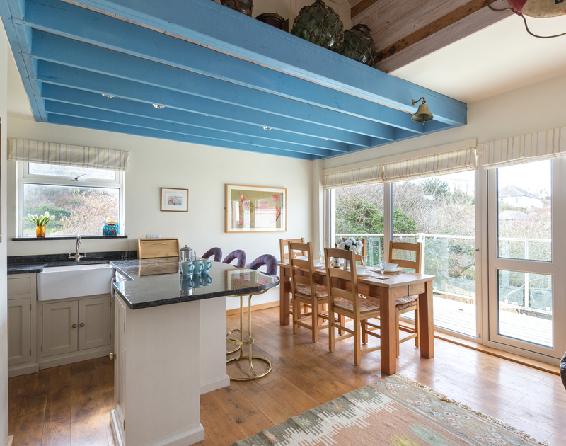 Big glass windows and a door out to the balcony make the kitchen/dining room bright and light at Beachside, a self catering holiday house in Polzeath in North Cornwall.