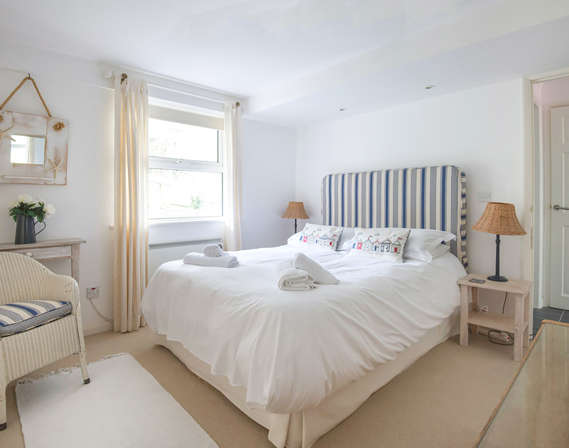 The attractive ground floor bedroom with King size bed and nautical feel in Slipway 19, a self catering holiday cottage in Rock, Cornwall.