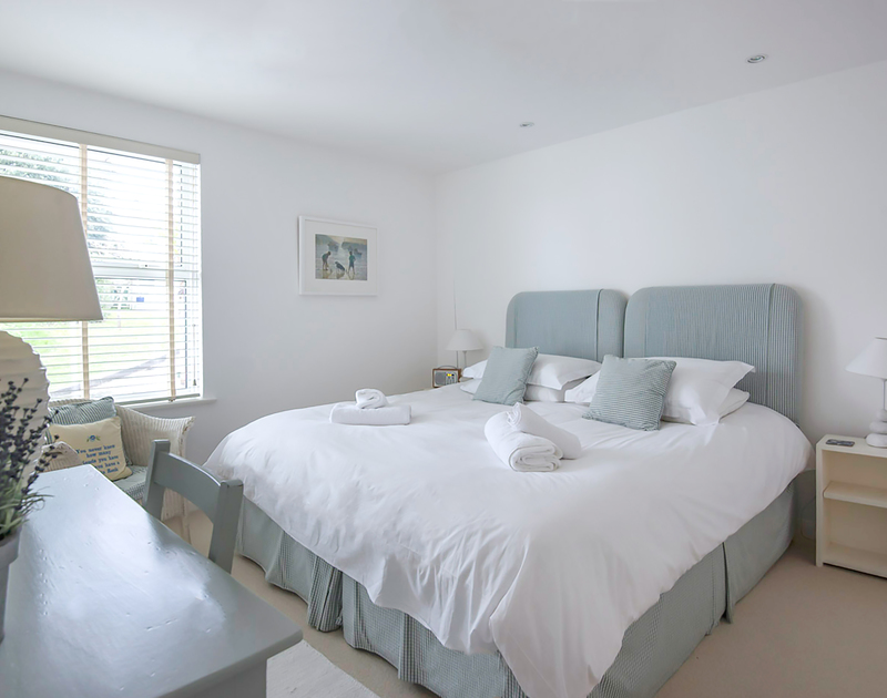 A comfortable, neutral bedroom on the ground floor with Super King size bed and en-suite bathroom in Slipway 19,  a spacious, self catering holiday cottage in Rock, North  Cornwall.