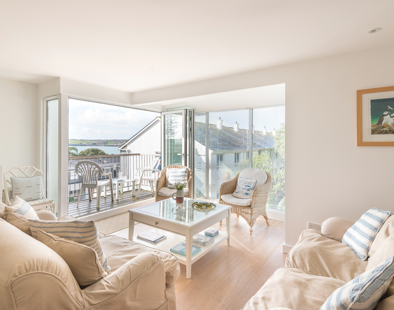 The comfortable sitting room with large glass patio doors onto the balcony and the Camel Estuary views beyond from Slipway 19, a holiday rental in Rock, Cornwall.