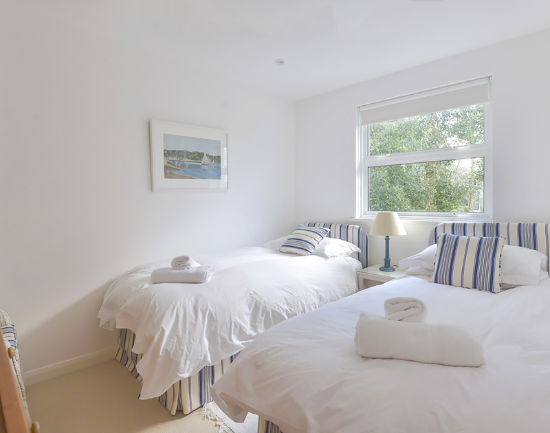 Two stripey upholstered twin beds in self catering, holiday rental Slipway 19 in Rock, Cornwall.