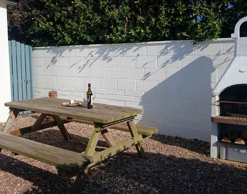 The sunny sheltered patio table and bar-b-que area at the self catering 2 bedroom holiday rental, Tamarisk in the lovely Port Isaac, North Cornwall.
