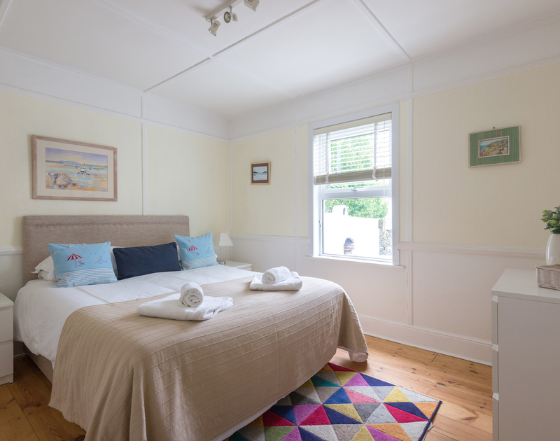 The master bedroom has a king size bed and warm wooden floorboards at Tamarisk, a self catering holiday cottage in Port Isaac.