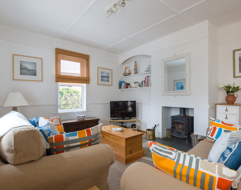 Relax in the welcoming sitting room with a wood burner at Tamarisk, a self catering holiday rental in Port Isaac, North Cornwall.