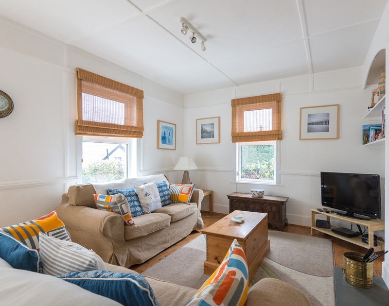 Dual aspect windows pour natural light into the comfortably furnished sitting room at Tamarisk, a self catering holiday cottage in Port Isaac, North Cornwall.