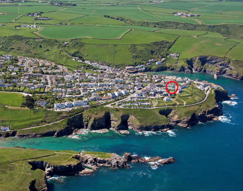 A high aerial view of the cliffside location of The Folly, a holiday rental in Port Isaac, Cornwall, with Port Gaverne cove in the foreground.