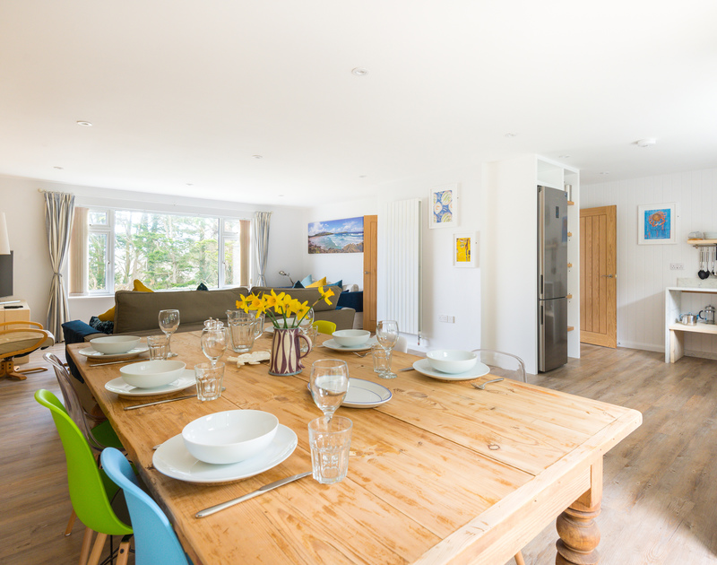 The dining table in the light, open plan living area at split level, recently refurbished, holiday house Beaches in Polzeath, North Cornwall.