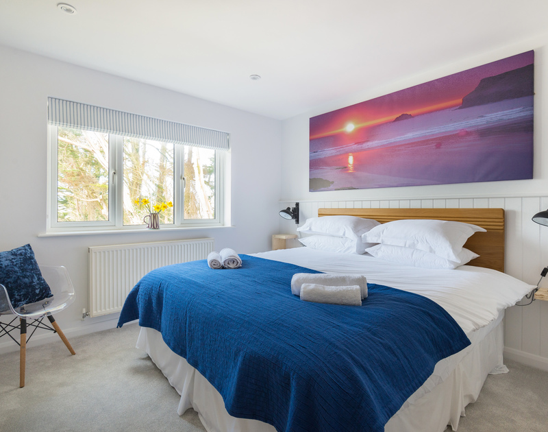 The double bedroom with a vast photograph above the bed of Polzeath at sunset which is just a short walk away from Beaches.