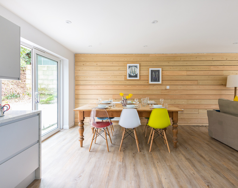 Stylish wood clad feature wall in the open plan dining room/kitchen at Beaches in Polzeath, Cornwall.