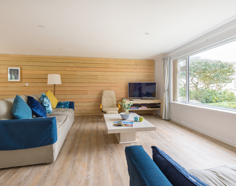 Relax in the chic and stylish sitting room at Beaches with a huge window filling the room with light in Polzeath, Cornwall.
