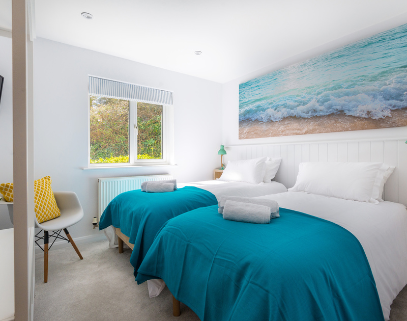 Relax in the twin bedroom at Beaches with a coastal theme only a few minutes walk from the real sea and sands on Polzeath Beach.