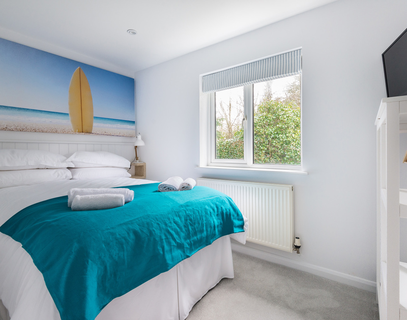 One of three bedrooms with a double bed at self catering holiday house Beaches in Polzeath.