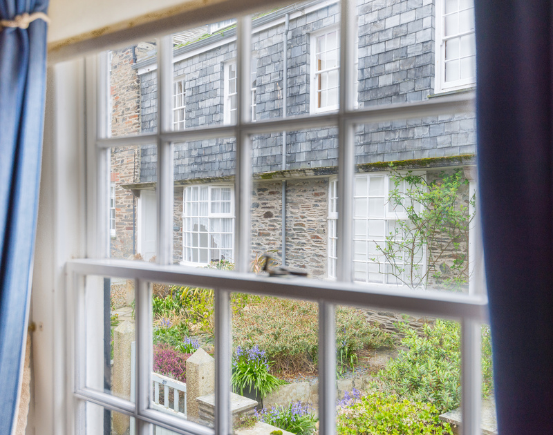 The view of gardens and pretty slate hung cottages through the sash window from the bunk bedroom at Temple Cottage in Port Isaac.
