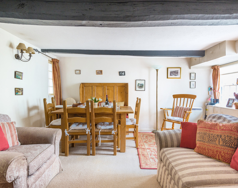 The open plan sitting room/dining room has original,exposed wooden beams in characterful holiday rental Temple Cottage in Port Isaac in Cornwall.