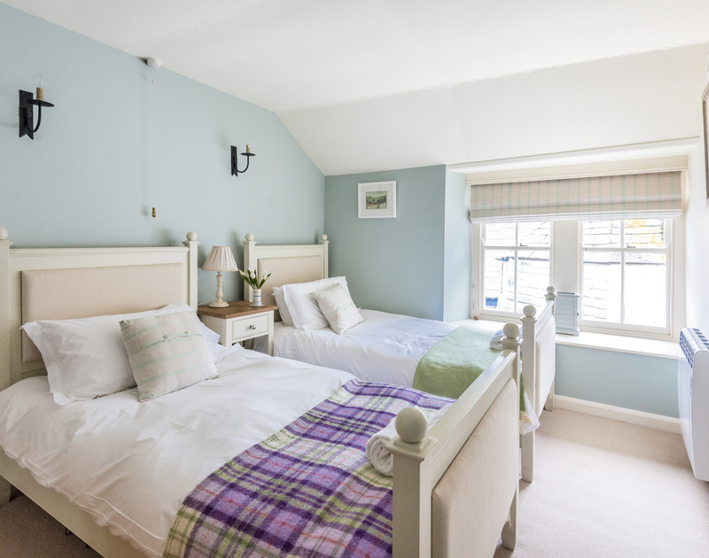 The twin bedroom has two wooden twin beds with upholstered headboards at Kicker Cottage, a beautifully presented, self catering holiday rental in the heart of the village of Port Isaac.