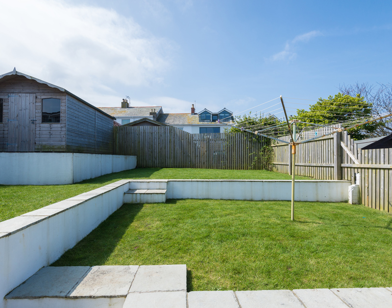 The sunny fenced garden has terraced lawns with room for everyone to play or relax and even the family pet is welcome to join the holiday at Tregenna in Port Isaac in North Cornwall.