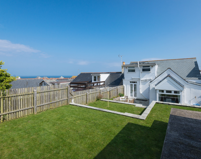 The sunny fenced garden has plenty of lawn space for peaceful sunbathing or family games at Tregenna, a self catering holiday house to rent in Port Isaac in North Cornwall.