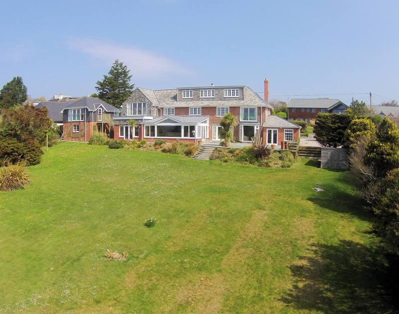 The exterior view and extensive lawns of Hob House, a large, superb holiday house at Daymer Bay, Cornwall with footpath from the end of the garden down to the beach