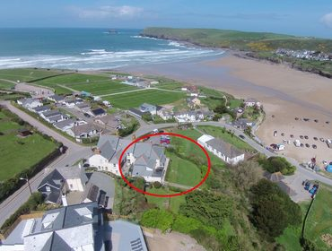 An aerial photo showing the house and gardens of Pentire View 3, a holiday house in Polzeath, Cornwall and its beachside location and large sunny gardens.