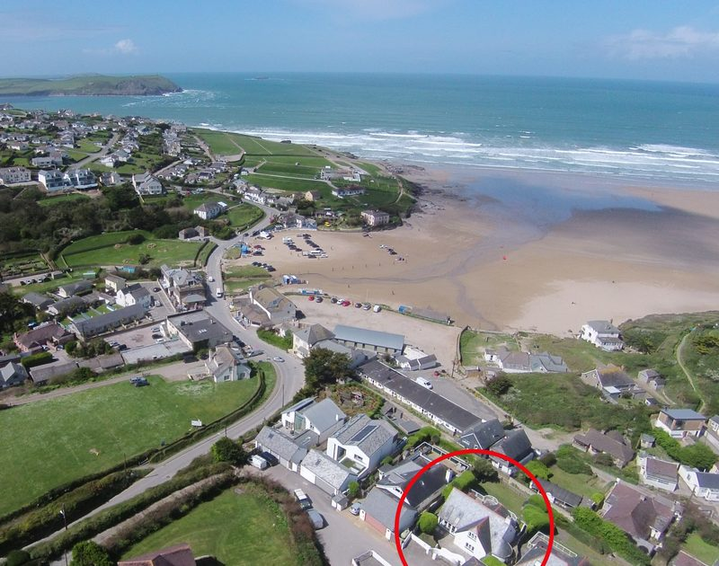 An aerial of house across the surf beach to the headlands of Pentire and Stepper beyond of Gunyah, a holiday rental in Polzeath, North Cornwall.